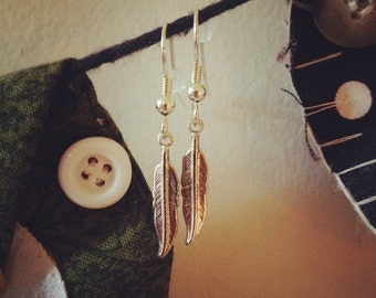 Silver colored feather earrings