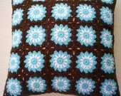 crocheted  granny square cushion cover in blue white and brown
