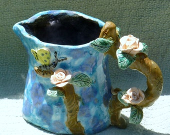 Unique hand buil no molds are ever used,t sweet pitcher with peach roses and butterfly pewter glaze inside  made in USA