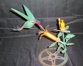 Scrap metal painted hummingbird and flowers sculpture
