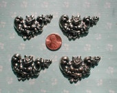 Four High relief silver toned decorative findings