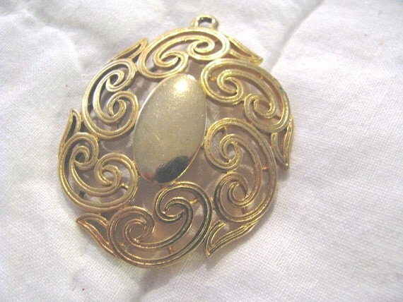 Goldtone scrollwork pendant.  1970s. two inches top to bottom with beautiful patina.