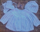 Baby's traditional blue lacy matinee jacket, cap and booties.