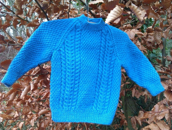 Childs boy's girl toddler blue aran cable sweater with back neck buttons.