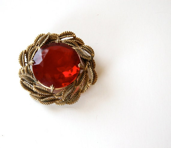 ruby red crystal brooch on a  bed of golden leaves