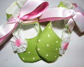 Mary Jane baby bootie shoes accented with a dainty  flower and pink button, white and pink ribbon ties in sizes newborn to 18 months