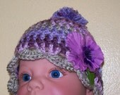 Crocheted Baby hat - verigated purples, blues, pinks and greens with pom and flower