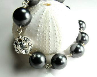 Swarovski Crystal grey pearls in sterling silver and adjustable closure...