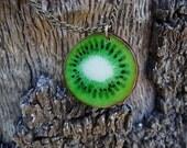 Medallón con cadena metálica de un kiwi  pintado a mano. Es posible personalizarlo detrás. Pieza unica.