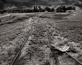 Abandoned Train Tracks Lead Toward a Stormy Sky