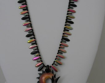 Dramatic handblown dichroic glass dragon pendant with daggers
