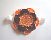 Frayed shabby flower orange and brown attached to a white headband.