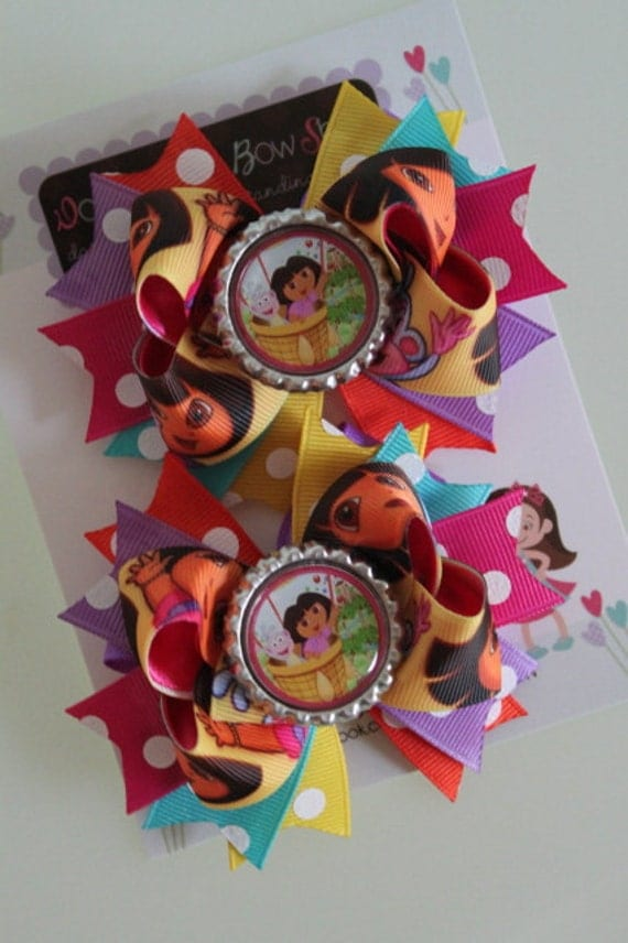 Dora pigtail bows -- Dora and Boots bottlecap bow -- lots of bright colors and polka dots-- for her Dora birthday
