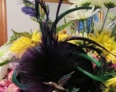 Cocktail hat.  A couture black and purple hair fascinator with a vintage bird brooch
