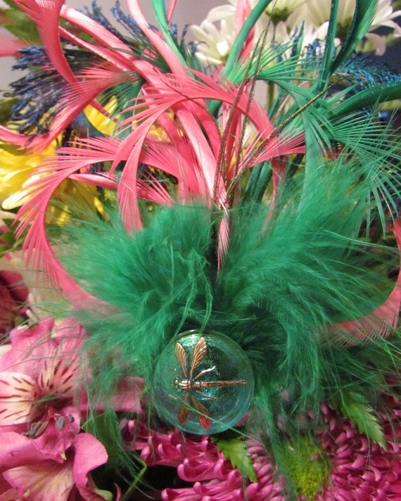 Green and pink feathered headpiece with a dragonfly glass button.