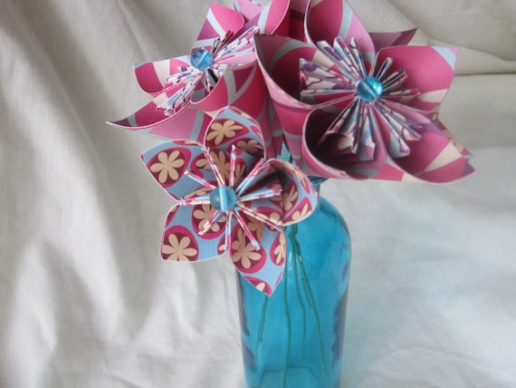 Bright pink and light blue paper flower arrangement in aqua blue vase