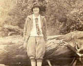 Vintage Photo - Young Woman in Knickers, Plaid Jacket & Tie, Hat, Leans on Big, Fallen Tree Trunk, Men's Style - RPPC postcard c. 1920s