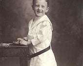 Vintage Photo - Portrait of Adorable Little Boy Missing His Front Teeth, in Sailor Tunic, Black Socks, Oversized Belt - early 1900s antique