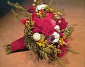Dried flower bouquet in burgundy, cream, and gold.