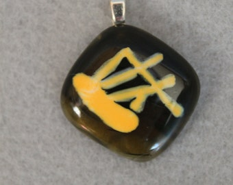 Fused glass pendant in dark green and yellow enamel
