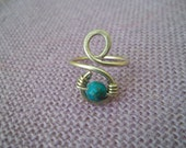 Handmade hammered silver wire ring with turquoise bead .