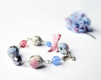 Blue and pink beaded bracelet, fabric, book pages, fabric and faceted glass beads