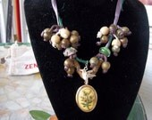 In the Herbal Garden Locket Necklace, Organic Cluster Interactive Necklace with hummingbird, twine, and silk
