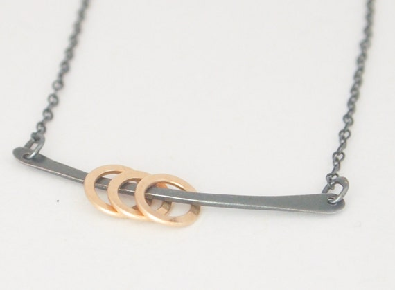 Mixed Metals Bar Necklace. Three delicate gold circles swing from an oxidized sterling silver chain.