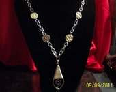 Modern style long necklace with silvertone disk and a wire wrapped design as a pendant