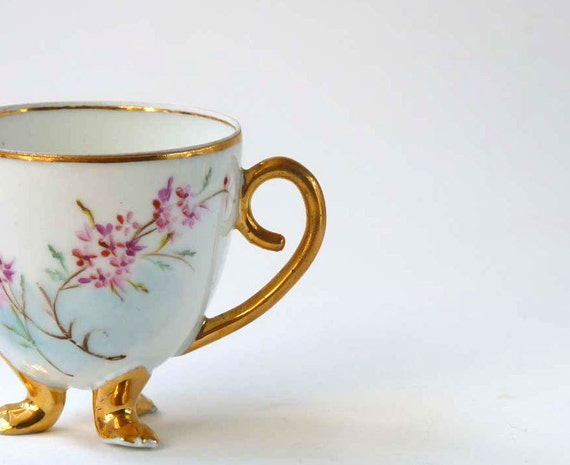 Antique Eggshell tea cup, footed with floral spray and gilt accents