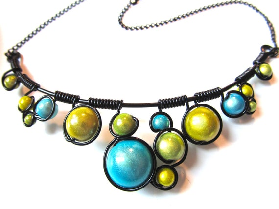 Wire wrapped necklace with pastel green and turquoise miracle beads, black wire and adjustable chain.