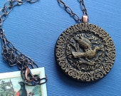 Antique/vintage button necklace featuring a perching songbird