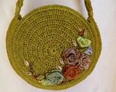 Green crochet handbag decorated with satin flowers
