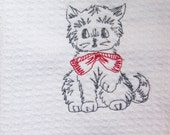 Flour sack towel with an embroidered gray kitty and a red bow.