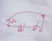 White flour sack towel embroidered with a pink pig