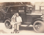 Vintage/Antique hoto of a happy couple sitting on a vintage car