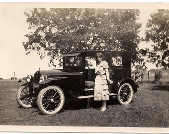 Vintage/Antique photo of  a woman in a dress with a vintage car