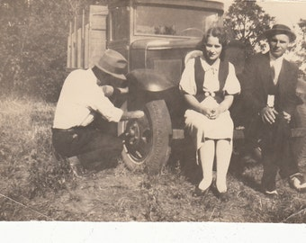 Vintage/Antique photo of men and a woman sitting on a farm truck