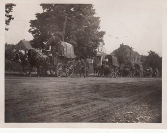Vintage/Antique photo of a parade of horse drawn covered wagons on a dirt road