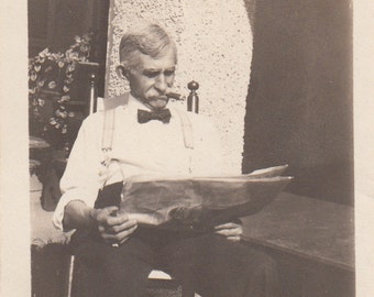 Vintage/Antique photo of an old man reading a newspaper and smoking a cigar