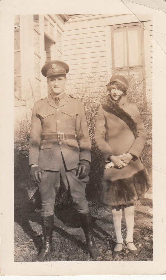 Vintage/ Antique photo of a cute couple wearing a furry coat and military or police uniform