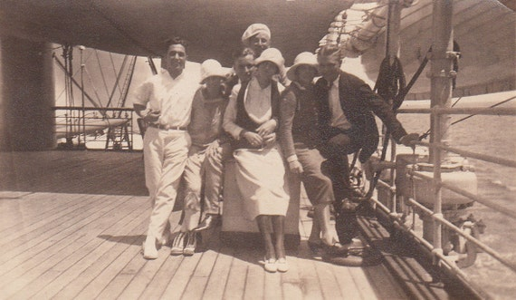 Vintage/ Antique photo of a group of men & women in a fancy outfits on a ship