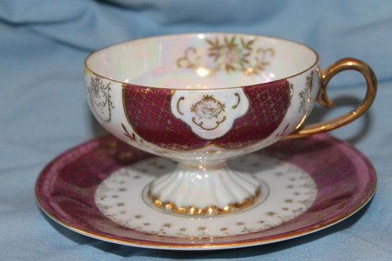 Teacup and saucer collectible pearlescent with gold edging and gold highlights
