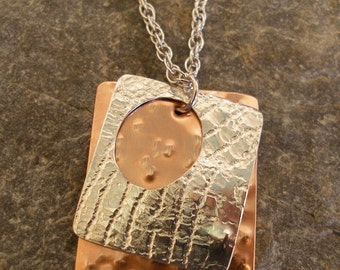 Sterling Silver and Copper Layered, Textured, Pendant Necklace with a large oval hole, hung on a silver chain