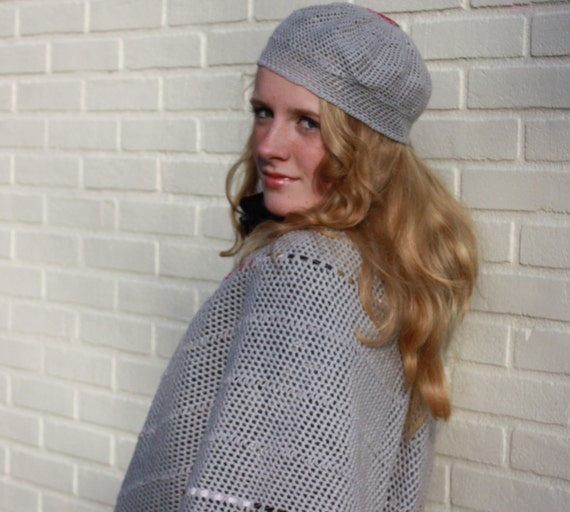 grey poncho with fabric woven in. Matching little hat. Also a matching bag in the shop