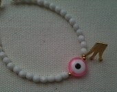 Beaded white bracelet with a pink evil eye and a Crown