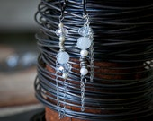 One of a kind dangle earrings featuring vintage white beads and silver colored chains