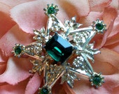 Star brooch with green glass rhinestones  detailed flowers and leaves possible metal is silverx sweet antique brooch