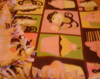 Fleece blanket, monkeys and cup cakes  on it,  other side is all light pink in color