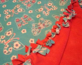 Fleece blanket with  butterflies and flowers on blue fleece , other side is dark pink,